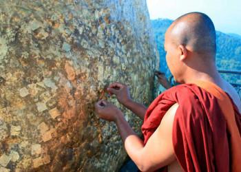 Mönch klebt Blattgold auf Golden Rock