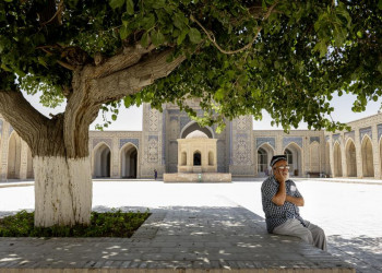 Usbeke vor einer Moschee in Chiwa, Usbekistan