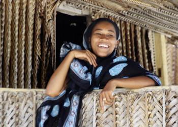 Lachende Frau vor einer Hütte auf Sansibar