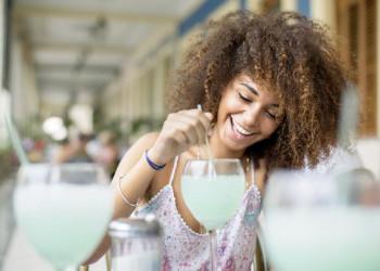 Fröhliche junge Kubanerin mit Cocktailglas in Havanna