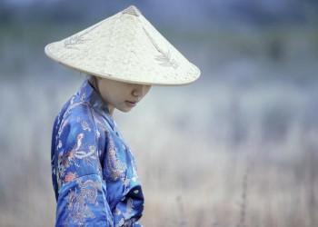 Anmutige Chinesin im bestickten Seidenmantel und mit Hut