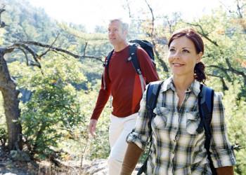 Ein im Wald wanderndes Paar mit Rucksäcken