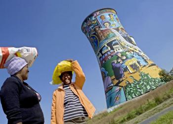 Frauen vor bemaltem Kühlturm in Soweto