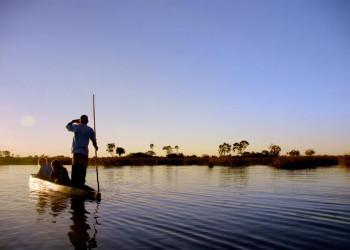 Sonnenuntergang auf einem Boot im Okavangodelta in Botswana
