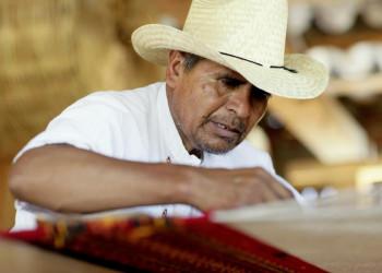 Ein Mann webt einen Teppich mit traditionellen mexikanischen Mustern