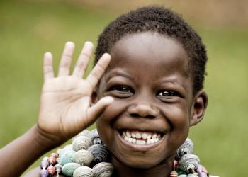 Fröhlich lachender kleiner Junge mit Ketten in Uganda