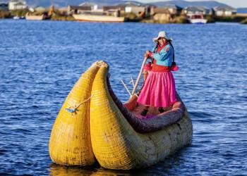 Uros-Frau auf einem Binsenboot auf dem Titicacasee