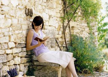 Lesende Frau auf einer Steinbank.