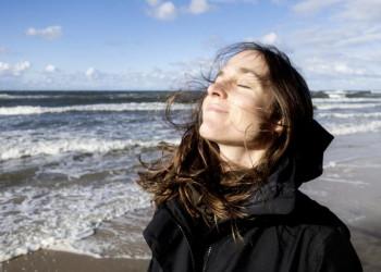 Frau mit geschlossenen Augen genießt die frische Meeresluft